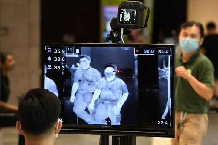 Petugas memeriksa para penumpang di Bandara Changi, untuk mendeteksi suhu tubuh penumpang. Foto: Roslan Rahman/AFP via Getty Images